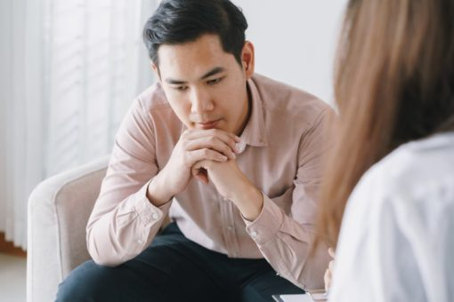 Male patient with woman therapist receiving psychotherapy in a clinic.